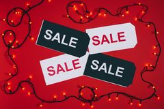 lägenheten lägger med prislappar med försäljningsbokstäver och julljus som isoleras på rött Arkivbild