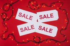 lägenheten lägger med prislappar med försäljningsbokstäver och julljus som isoleras på rött Arkivbilder