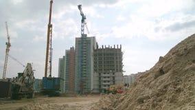 Lägenhetkonstruktionsplats med den gula kranen plats Ny hyreshus under konstruktion på solig dag på blått arkivfilmer