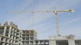 Lägenhetkonstruktionsplats med kranen kran för byggnadskonstruktion lager videofilmer