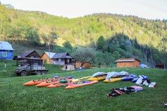 Läger av vattenlegeringar och kajaker som torkar på gräset i den Carpathian byn på bakgrunden av berg arkivfoto
