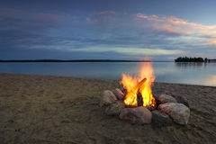Lägerbrand på den sandiga stranden, bredvid sjön på solnedgången Minnesota USA royaltyfri bild