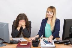 Läget i kontoret - en flicka är mycket uppriven, andra är nätt rätar ut saker på ditt skrivbord arkivbilder