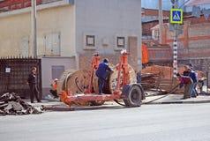 Lägga av en elektrisk kabel under kommunal service för asfalt samara Royaltyfri Bild