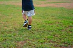 Lägga benen på ryggen eller fäll ned kroppsdelen av ungen som går eller, kör på gräsfält eller l arkivfoton