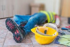 Lägga benen på ryggen och gulna hjälmen av den sårade liggande arbetaren på arbete arkivbild