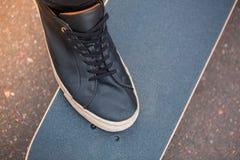 Lägga benen på ryggen på skateboarden i svarta gymnastikskor och svärta brädet arkivbild