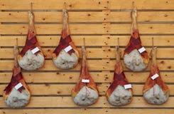 Lägga benen på ryggen skinkor av prosciuttoen San Daniele, en utmärkt italiensk rå skinkakvalitet som hänger på en trävägg royaltyfri fotografi