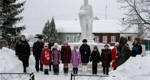 Lägga blommor och begravnings- kransar på en massgrav i den Kaluga regionen i Ryssland Royaltyfria Foton