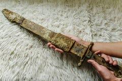 Lägga det antika verkliga svärdet på en handgjord ullfilt royaltyfri foto