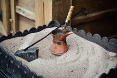 Lägga in för förberedelse av turkiskt kaffe på varm sand Royaltyfri Fotografi