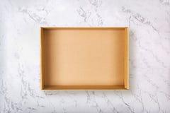 Lägga framlänges av den tomma kartongen på naturlig marmortextur fotografering för bildbyråer