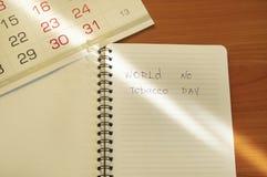 Lägga framlänges, cigaretter och inskriftvärlden ingen skriftlig tobakdag i en anteckningsbok, en sund livsstil utan royaltyfria foton