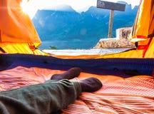 Lägga ner i ett tält framme av ett berg royaltyfri foto