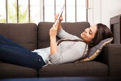 Lägga på en soffa och en läsning royaltyfri bild
