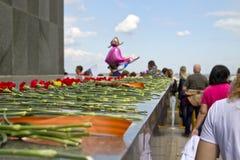Lägga röda nejlikor på foten av skulpturen av modern Royaltyfria Foton