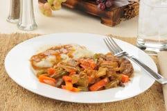 Lägga in stek och potatisar Royaltyfri Bild