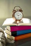 Läggdagsläsning, ringklocka och böcker Royaltyfria Foton