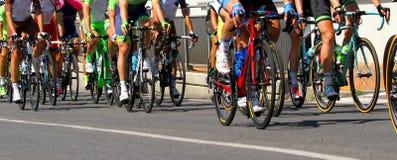 Lägger benen på ryggen av cyklister som rider under loppet Arkivbild