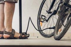 Lägger benen på ryggen av en man i sportsandaler som blåser upp cykelgummihjul med p royaltyfria foton