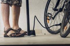 Lägger benen på ryggen av en man i sportsandaler som blåser upp cykelgummihjul med p arkivbilder