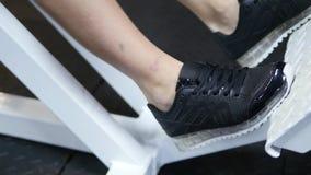Lägger benen på ryggen av en ung kvinna som utbildar på idrottshallen stock video