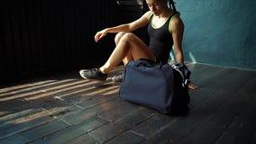 Lägger benen på ryggen den färdiga unga kvinnan för ultrarapid skrivande in idrottshall med påsen och att förbereda sig för utbil lager videofilmer
