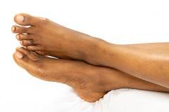 Lägger benen på ryggen den kvinnliga foten för afrikansk amerikan hälet av foten som isoleras på en vit bakgrund för medicinskönh arkivfoto