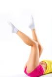 Lägger benen på ryggen den spensliga konditionflickan - som isoleras på vit Arkivbild