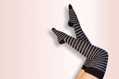 Lägger benen på ryggen flickan med randiga strumpor Arkivfoton