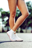 Lägger benen på ryggen i gymnastikskor Arkivfoton