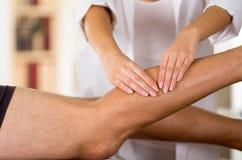 Lägger benen på ryggen kvinnliga physio terapeuthänder för closeupen som arbetar på manliga patienter, oskarp klinikbakgrund Arkivbilder