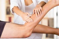 Lägger benen på ryggen kvinnliga physio terapeuthänder för closeupen som arbetar på manliga patienter, oskarp klinikbakgrund royaltyfria foton