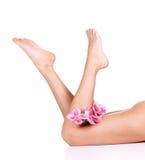 Lägger benen på ryggen kvinnligt slankt för skönhet Arkivbild