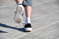 Lägger benen på ryggen löparepojken i gymnastikskor Arkivfoton