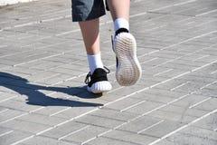 Lägger benen på ryggen löparepojken i gymnastikskor Royaltyfri Foto