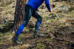 Lägger benen på ryggen manligt köra för idrottsman nen som är stigande Royaltyfri Foto