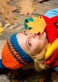 Lägger den gladlynta framsidan för flickan på träbakgrund med bästa sikt för orange sidor Angenäma ögonblick Nedgång och höstsäso royaltyfria foton