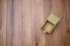 Lägger den tomma öppna kartongen för asken på träyttersida med den bästa lägenheten för tomt utrymme arkivfoto