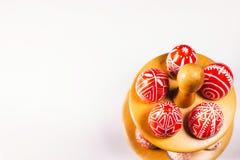 Lägger röda ägg för Closeuppåsk med den folk vita modellen omkring på ställningen för ägg som står i ner sida på vit bakgrund Ukr arkivbilder