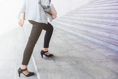 Lägre del av den funktionsdugliga kvinnan för benaffär som går upp trappan på av Arkivfoton