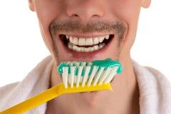 Lägre del av framsidan av mannen med den stora gula tandborsten och vithandduken på skuldror Royaltyfria Bilder