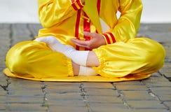 Lägre del av kvinnan som sitter i lotusblommaposition royaltyfri foto