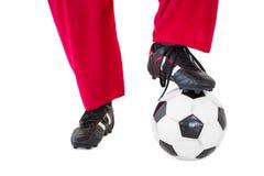 Lägre - halva av santas ben med fotbollkängor och fotboll Arkivfoto