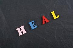 LÄKA ordet på svart brädebakgrund som komponeras från träbokstäver för färgrikt abc-alfabetkvarter, kopieringsutrymme för annonst Royaltyfri Fotografi