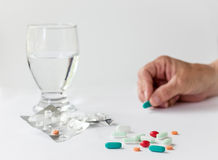 Läkarbehandling och preventivpillerar med exponeringsglas av vatten Arkivbilder
