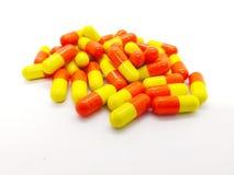Läkarbehandling och sjukvårdbegrepp Många apelsin-guling capsules nolla royaltyfria foton