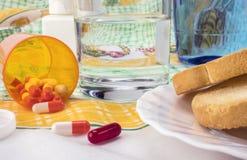 Läkarbehandling under frukosten, kapslar bredvid ett exponeringsglas av vatten, begreppsmässig bild arkivfoto