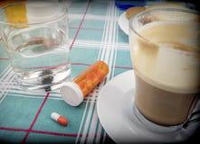 Läkarbehandling under frukosten, kapslar bredvid ett exponeringsglas av vatten, begreppsmässig bild royaltyfria foton