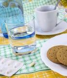 Läkarbehandling under frukosten, kapslar bredvid ett exponeringsglas av vatten, begreppsmässig bild royaltyfria bilder
